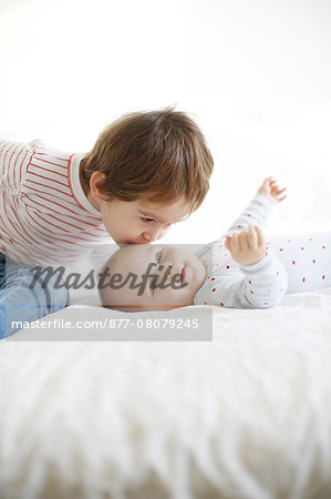 A little boy of 4 years old kissing on the head his baby sister of 10 months Stock Photo - Rights-Managed, Image code: 877-08079245