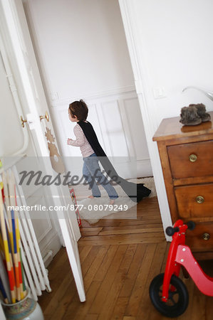 Little boy playing with a black cape, he runs in a hallway Stock Photo - Rights-Managed, Image code: 877-08079249
