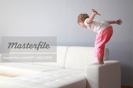 France,  4 years old girl on sofa arm. Stock Photo - Rights-Managed, Image code: 877-08127997