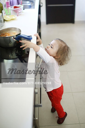 A 2 years old little girl is about to catch a saucepan on the hob Stock Photo - Rights-Managed, Image code: 877-08129098