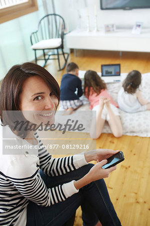 Family using different electronic devices in their living room Stock Photo - Rights-Managed, Image code: 877-08129216