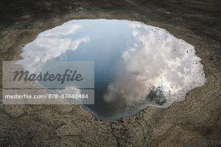 Rain drops falling onto a large puddle. A reflection of sky and clouds. Stock Photo - Rights-Managed, Image code: 878-07442484