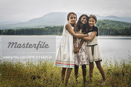 Three young girls standing by the side of a lake, hugging each other. Stock Photo - Rights-Managed, Image code: 878-07442514