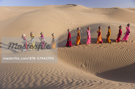 Women bear the responsibility of fetching water from the sparse wells within Rajasthan's vast Thar Desert. Trekking up the side of a sand dune, women expertly balance large clay water vessels atop their heads. Rajasthan, India Stock Photo - Rights-Managed, Image code: 878-07442705