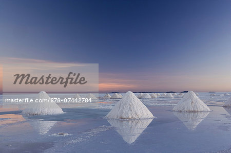 The salt pans of Salar de Uyuni, with shallow water and mineral deposits. White salt granules raked into heaps. Stock Photo - Rights-Managed, Image code: 878-07442784