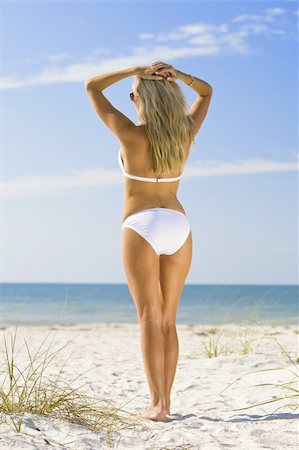 simsearch:400-04002563,k - A beautiful young blond woman wearing a white bikini looks out to sea across a beautiful sandy beach Stock Photo - Budget Royalty-Free & Subscription, Code: 400-04002563
