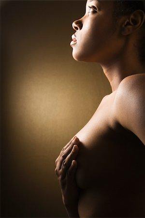 Young adult African-American female giving self breast exam. Stock Photo - Budget Royalty-Free & Subscription, Code: 400-04002643