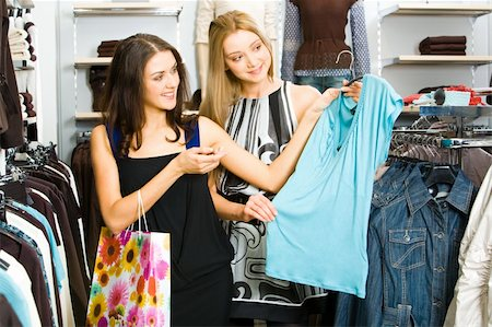 Portraits of two friends in the clothing department looking at new T-shirt and choosing new clothes Stock Photo - Budget Royalty-Free & Subscription, Code: 400-04015733
