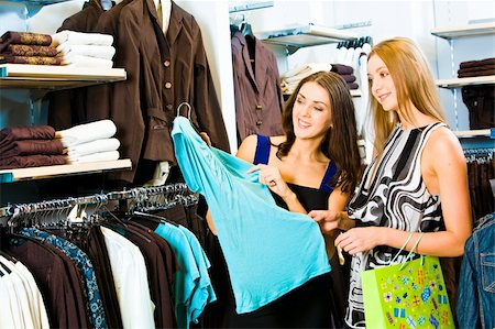 Photo of two girls in the clothing store holding a blue dress and looking at it with smiles on the background of different clothes Stock Photo - Budget Royalty-Free & Subscription, Code: 400-04011457