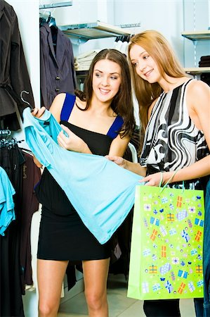 Portrait of two friends in the shopping centre standing in the clothing department with a blue dress in hands Stock Photo - Budget Royalty-Free & Subscription, Code: 400-04011459