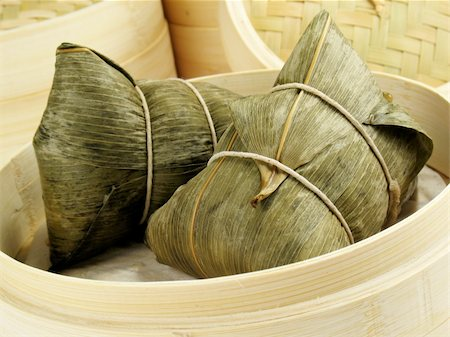 dumplings steamer - Steamed Chinese rice dumplings (zongzi) wrapped in bamboo leaves, filled with glutinous/sticky rice, pork, mushrooms, and peanuts. These are eaten during the Dragon Boat Festival. Stock Photo - Budget Royalty-Free & Subscription, Code: 400-04025064