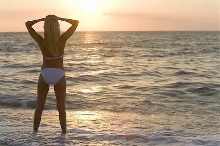 simsearch:400-04002563,k - A beautiful bikini clad blond stands in the surf at sunset Stock Photo - Budget Royalty-Free & Subscription, Code: 400-04020397