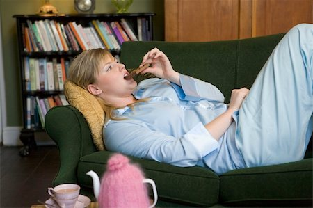 A young woman lying on her couch eating chocolate Stock Photo - Budget Royalty-Free & Subscription, Code: 400-04037414