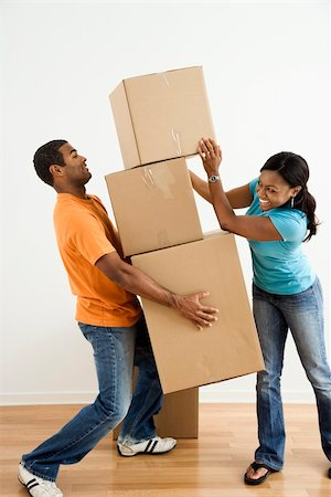 African American female placing boxes on large stack man is holding. Stock Photo - Budget Royalty-Free & Subscription, Code: 400-04039742