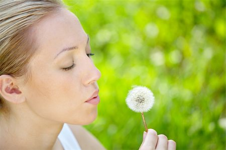 The girl blows on a dandelion on a background of a grass Stock Photo - Budget Royalty-Free & Subscription, Code: 400-04031864