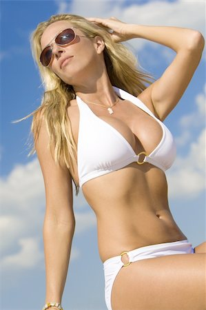 simsearch:400-04002563,k - A beautiful young blond woman wearing a white bikini and sunglasses shot against a blue sky Stock Photo - Budget Royalty-Free & Subscription, Code: 400-04049374