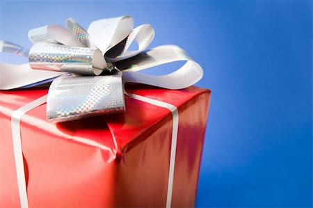 simsearch:400-05749231,k - Macro of red giftbox top decorated with bow made up of silver ribbon Stock Photo - Budget Royalty-Free & Subscription, Code: 400-04056479