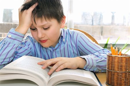 Serious school boy studying with a book Stock Photo - Budget Royalty-Free & Subscription, Code: 400-04059184