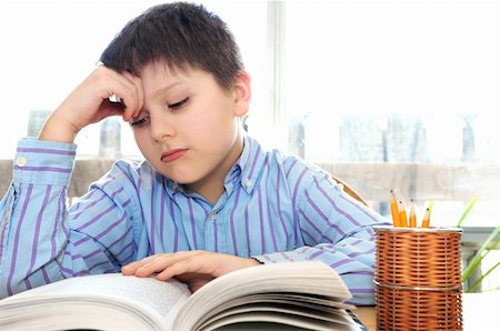 Serious school boy studying with a book Stock Photo - Budget Royalty-Free & Subscription, Code: 400-04059185