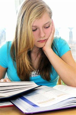 Teenage girl studying with textbooks looking unhappy Stock Photo - Budget Royalty-Free & Subscription, Code: 400-04059956