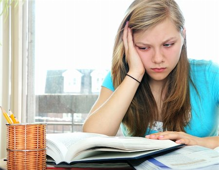 Teenage girl studying with textbooks looking unhappy Stock Photo - Budget Royalty-Free & Subscription, Code: 400-04059957