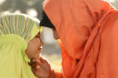 daughter kissing mother - Muslim mother and child   looking at each other Stock Photo - Budget Royalty-Free & Subscription, Code: 400-04053917