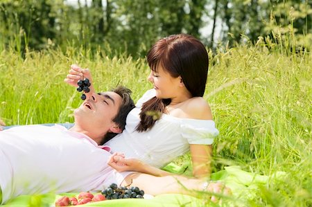 Couple lying in grass, smiling and eating grapes Stock Photo - Budget Royalty-Free & Subscription, Code: 400-04066408