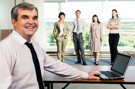 Photo of older smiling leader touching the laptop on the background of working team Stock Photo - Budget Royalty-Free & Subscription, Code: 400-04071696