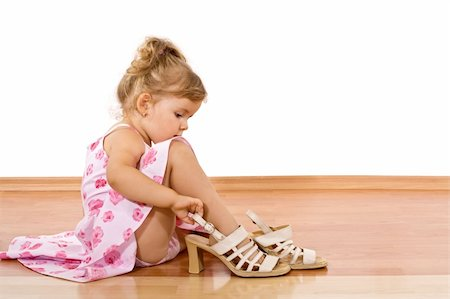 Little girl trying her mother's shoes on the floor - isolated Stock Photo - Budget Royalty-Free & Subscription, Code: 400-04073107