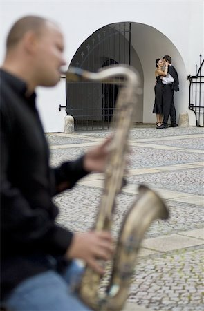 Selective focus shot of a street musician playing his saxophone while a romantic couple kiss in the background Stock Photo - Budget Royalty-Free & Subscription, Code: 400-04082044