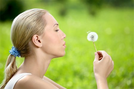 The blonde sits in park on a grass with a dandelion in hands Stock Photo - Budget Royalty-Free & Subscription, Code: 400-04107729