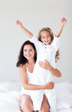 daughter kissing mother - Young Mother and daugther embracing on bed Stock Photo - Budget Royalty-Free & Subscription, Code: 400-04108146