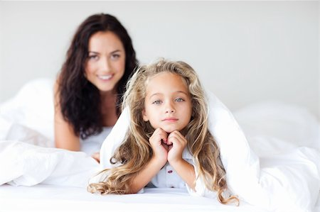 daughter kissing mother - Young Mother and daugther embracing on bed Stock Photo - Budget Royalty-Free & Subscription, Code: 400-04108149