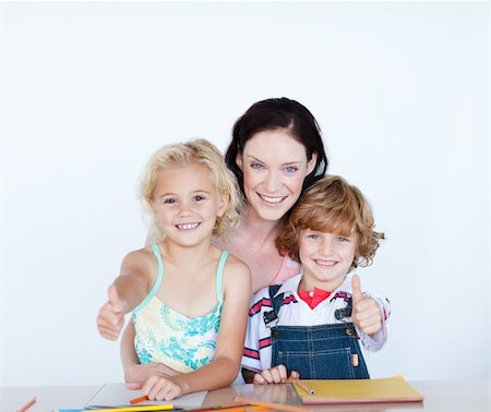 Happy children doing homework with their mother with thumbs up Stock Photo - Budget Royalty-Free & Subscription, Code: 400-04118369