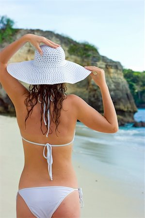 Beautiful brunette with long hair in white hat stands on the sand ocean beach on Bali in Indonesia Stock Photo - Budget Royalty-Free & Subscription, Code: 400-04127673