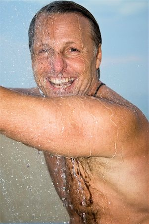 A colour portrait of a happy smiling forties man washing and having fun under the shower. Stock Photo - Budget Royalty-Free & Subscription, Code: 400-04120881