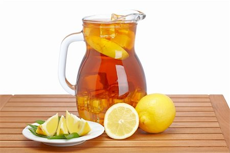 Ice tea pitcher with lemon and icecubes on wooden background Stock Photo - Budget Royalty-Free & Subscription, Code: 400-04121373