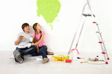 Image of attractive couple sitting on floor during lunch break and looking at green heart on wall Stock Photo - Budget Royalty-Free & Subscription, Code: 400-04148669