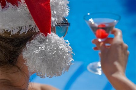 spanishalex (artist) - Woman drinking a martini cocktail by the side of a beautiful blue pool in a santa hat Stock Photo - Budget Royalty-Free & Subscription, Code: 400-04150542