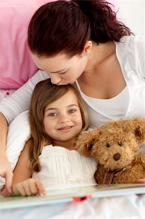daughter kissing mother - Mother kissing her daughter reading a book  in bed Stock Photo - Budget Royalty-Free & Subscription, Code: 400-04151213