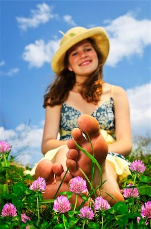 Young teenage girl sitting on summer meadow amid wildflowers in straw hat Stock Photo - Budget Royalty-Free & Subscription, Code: 400-04163242