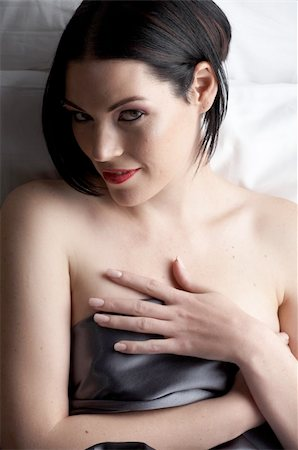 Sexy naked young caucasian adult woman with red lips, short black hair and a pierced eyebrow, covered in a dark satin sheet and sitting on a bed Stock Photo - Budget Royalty-Free & Subscription, Code: 400-04173283