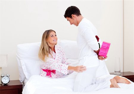 Enamoured husband giving a present to his wife in the bedroom Stock Photo - Budget Royalty-Free & Subscription, Code: 400-04195862
