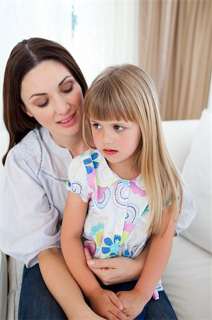 daughter kissing mother - Cute blond girl sitting on her mother's lap in the living-room Stock Photo - Budget Royalty-Free & Subscription, Code: 400-04197573