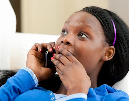 Astonished afro-american teenager talking on phone lying on a sofa Stock Photo - Budget Royalty-Free & Subscription, Code: 400-04206775