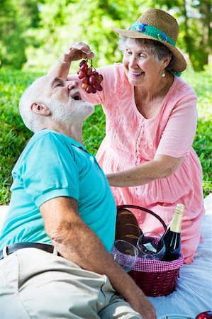Senior couple on a romantic picnic in the park.  She is feeding him grapes. Stock Photo - Budget Royalty-Free & Subscription, Code: 400-04208630