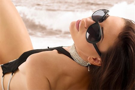 brunette sexy girl with long hair wearing a black swimsuit and sunglasses laying down on white Stock Photo - Budget Royalty-Free & Subscription, Code: 400-04202105