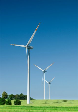 three wind turbines on green field, cloudless sky behind Stock Photo - Budget Royalty-Free & Subscription, Code: 400-04212430