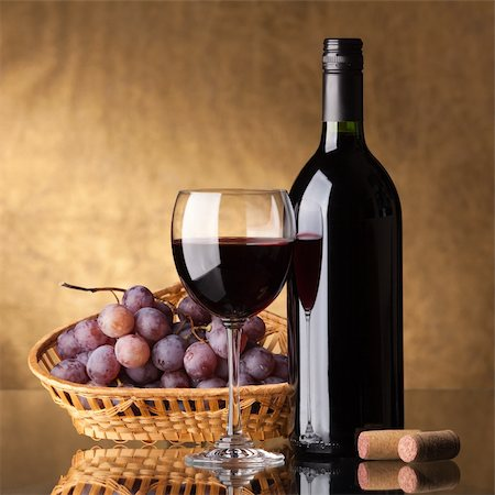 A bottle of red wine, glass and grapes on a golden background Stock Photo - Budget Royalty-Free & Subscription, Code: 400-04226436