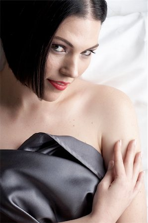 Sexy naked young caucasian adult woman with red lips, short black hair and a pierced eyebrow, covered in a dark satin sheet and sitting on a bed Stock Photo - Budget Royalty-Free & Subscription, Code: 400-04236124